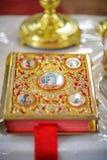 Attributo della chiesa una bibbia dorata con un fissare l'altare, vangelo, segnalibro santo e rosso Fotografia Stock Libera da Diritti