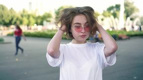 Attrice in occhiali da sole rosa che sorride alla macchina fotografica nel parco di estate, ciac video d archivio