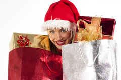 Attrractive Santa girl with presents bags. Rich, colorful series of attractive young woman in santa's hat with presents Royalty Free Stock Photos