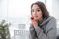 Attrractive young lady dressed in sweater sitting in cafe Stock Photos