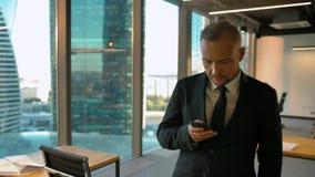 Attrtactive entreprenör i formellt dräktanseende nära fönster- och handstilsms stock video