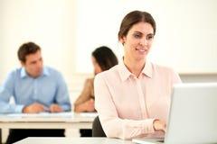 Atttractive jonge vrouw die aan haar laptop werken stock foto
