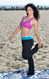 Atttractive woman working out on beach. Attractive brunette woman works out on beach - wearing pink sports bra - standing on yoga mat doing leg stretch Royalty Free Stock Photography