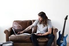 Attuatore caucasico dei pantaloni a vita bassa che lavora ad un computer portatile fotografia stock