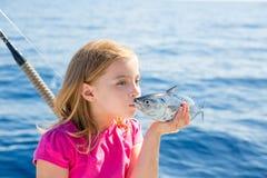 Atuns pequenos do atum louro da pesca da menina da criança que beijam para a liberação Foto de Stock