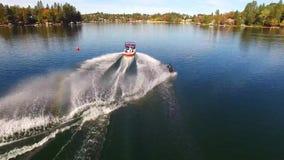 Aturdiendo la opinión aérea 4k sobre el esquiador de sexo masculino profesional del agua que se desliza en el lago azul tranquilo metrajes
