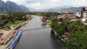 Aturdiendo la opini?n a?rea dos turistas que kayaking en el r?o que corre a trav?s del pueblo de Vang Vieng Vang Vieng almacen de video