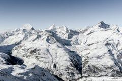 Aturdiendo la vista de las montañas alpinas del invierno ajardine en día brillante soleado en Suiza fotografía de archivo