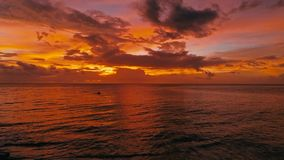 Aturdindo a imagem aérea bonita do zangão de um por do sol tropical vermelho acima do oceano do mar com o homem dois em uma pesca imagens de stock