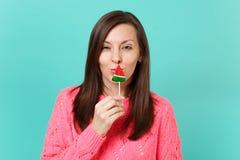 Aturdindo a jovem mulher na camiseta cor-de-rosa feita malha que guarda o pirulito disponivel da melancia perto da boca isolada n imagem de stock