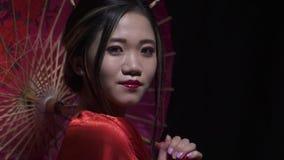 Aturdindo a mulher oriental com olhares e sorrisos cor-de-rosa do guarda-chuva vídeos de arquivo