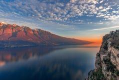 Aturdindo o por do sol no lago Garda Vista dos cumes nevados pintados pelo sol de ajuste do penhasco da cidade Tremosine Inverno fotos de stock