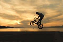 Aturdindo truques do motociclista do bmx contra o por do sol Fotos de Stock