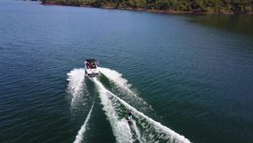 Aturdir la opinión aérea del abejón 4k sobre el esquí acuático de la persona ató al barco de motor en paisaje marino tropical del almacen de metraje de vídeo