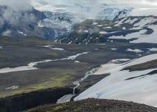 Aturdir la opinión sobre el glaciar de Myrdalsjokull con el río y la pequeña cascada, viaje de Fimmvorduhals de Skogar a Thorsmor imagenes de archivo