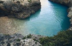 Aturdir la playa abandonada con agua azul imagenes de archivo
