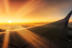 Aturdir la salida del sol que viaja sobre las nubes en el avión con los rayos de sol sobre las alas a través de ventana fotografía de archivo