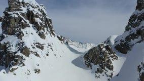 Aturdir las montañas con las colinas nevadas rocosas, cantidad aérea en 4k metrajes