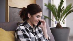 Aturdir, menina feliz com cauda do cabelo e composição falando no telefone ao sentar-se no sofá, extremidades a conversa com a vídeos de arquivo