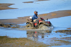 ATV骑马在泥和水中 免版税库存照片