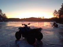 Atv на льде в заходе солнца стоковое изображение rf