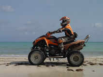 Atv on the beach in Haiti. A four wheels atv motorcycle on a beautiful beach in the Caribbean more specifically in Haiti. Rider: Robert Thomas royalty free stock photo