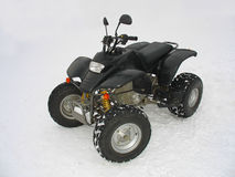 ATV Black All Terrain Vehicle on white snow. Background Stock Photos