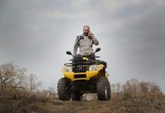 ATV-chaufför som talar på telefonen, medan köra Fotografering för Bildbyråer