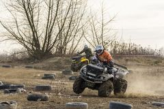 ATV-chaufförjämvikterna på två rullar in en krökning Arkivfoton