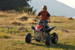ATV competition. Young boy racing ATV for fun Stock Image