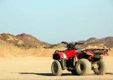 ATV dans le désert dans la perspective des montagnes Safari sur des vélos de quadruple Image libre de droits