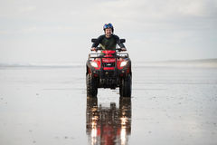 ATV driver on the beach. Happy ATV driver on the Ninety Mile Beach, New Zealand Stock Images