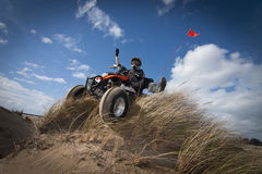 ATV en la duna de arena herbosa Imágenes de archivo libres de regalías