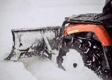 ATV i snön Göra ren gatorna av snö med en traktor royaltyfri foto