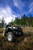 ATV in the mountains. ATV parked in a grassy field waiting to be ridden. Beautiful cloudscape in background. Good ad copy space available Royalty Free Stock Photography