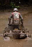 ATV in the mud. An ATV rider stuck in the mud Royalty Free Stock Image