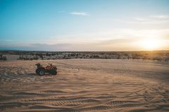 ATV Quad Bike in front of sunrise in the desert. ATV stands in the sand on a sand dune in the desert of Vietnam. MUI ne. ATV Quad Bike in front of sunrise in the royalty free stock photos