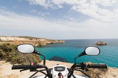 ATV quad bike parked on the shore of Aegean sea on Milos island, Greece. View from driver seat royalty free stock photos