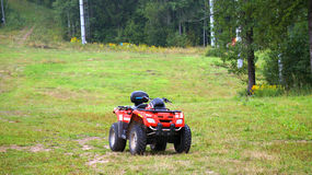 ATV Quad. Red awd quad bike parked on the green hill Royalty Free Stock Photography