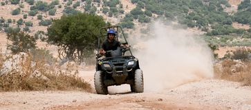 ATV quad runner. Rider on his four wheel ATV riding over the sand and rocks in the desert Royalty Free Stock Photo