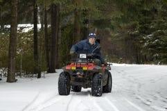 ATV quad senior rider. Senior male riding a  four wheel ATV over the snow. See the wheels moving Stock Photos
