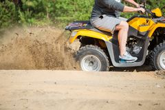 ATV quadbike在森林附近陷在一条含沙路和做浪花的有轮子旋转沙子 免版税图库摄影