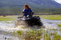 ATV Race. Woman on ATV, all terrain vehicle, racing through shallow water with mountains and meadow in background royalty free stock photos