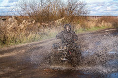 ATV race, dirty road. Uncnown driver in water and mud Stock Photo