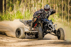 ATV racer takes a turn during. A race on a dusty terrain Stock Image