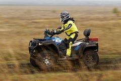 ATV-racerbil på en grusväg till och med fälten royaltyfria bilder