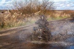 ATV rasa, brudna droga Uncnown kierowca w wodzie i błocie Zdjęcie Stock