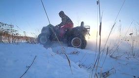 ATV-Reiten im langsamen Schießen der Schneehintergrundbeleuchtungs-Geschwindigkeit stock video