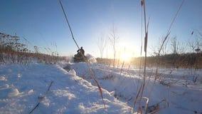 ATV-Reiten im langsamen Schießen der Schneehintergrundbeleuchtungs-Geschwindigkeit stock video footage