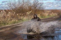 ATV-Rennen, schmutzige Straße Uncnown-Fahrer im Wasser und im Schlamm Lizenzfreie Stockbilder